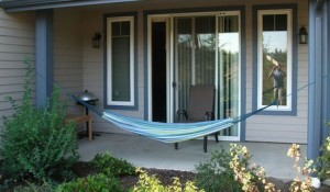 A comfortable summer hammock tied to 2 posts on the porch.